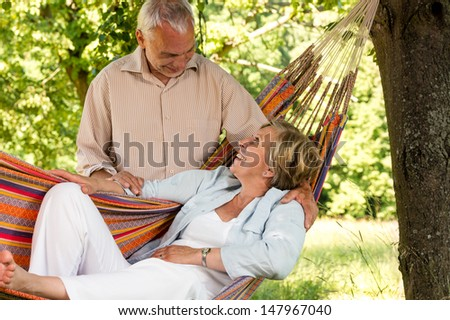 Happy senior couple relax hammock outdoors looking at each other - stock photo