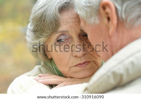 Happy senior couple relax in autumn park - stock photo