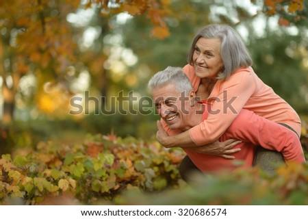 Happy senior couple relax in autumn park - stock photo