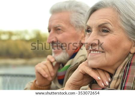 Happy senior couple relax in autumn park near river - stock photo