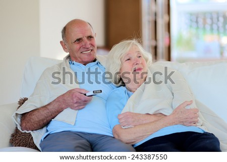 Happy senior couple relaxing at home sitting on sofa wrapped in soft plaid and watching tv