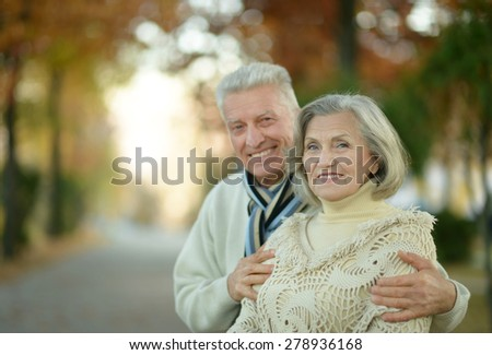 Happy senior couple relaxing in autumn park - stock photo