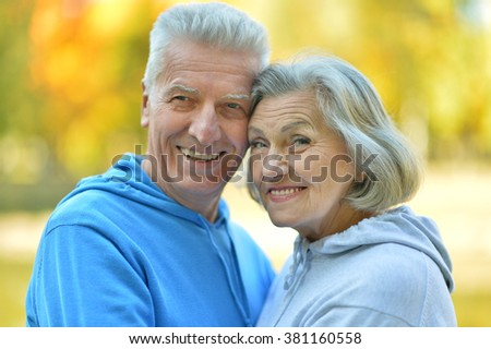 Happy senior couple relaxing in autumn park - stock photo