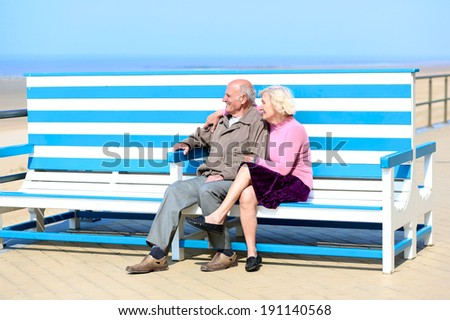Happy senior couple relaxing on the beach sitting together on the bench - active retirement concept - stock photo