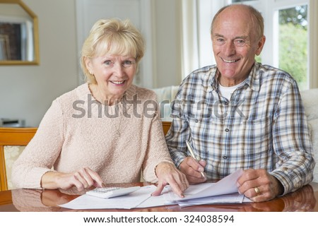 Happy Senior Couple reviewing Domestic Finances Together - stock photo
