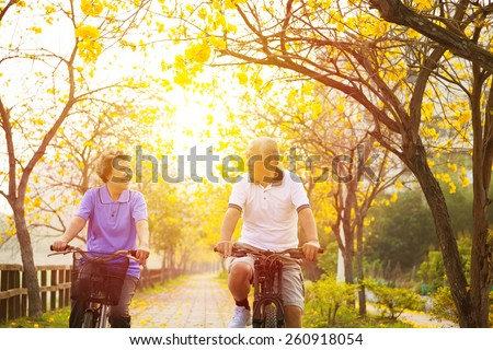 happy senior couple ride on bicycle  in the park - stock photo