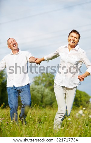 Happy senior couple running in summer over a grean meadow - stock photo