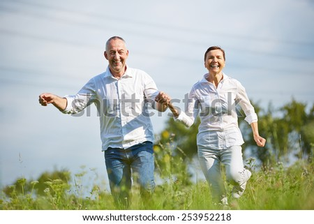 Happy senior couple running over meadow in summer - stock photo
