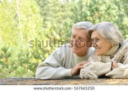Happy senior couple sitting at table in forest - stock photo