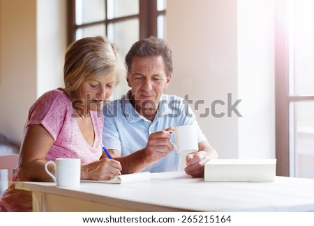 Happy senior couple sitting at the table making plans and drinking coffee in their living room. - stock photo