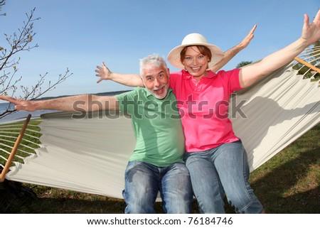 Happy senior couple sitting in hammock - stock photo