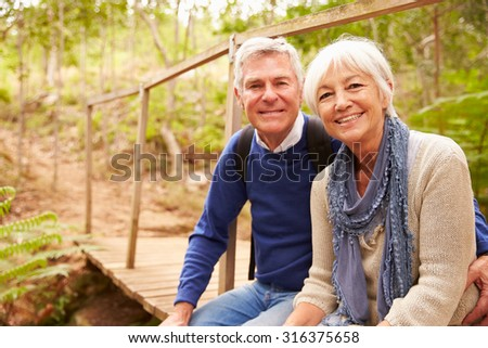 Happy senior couple sitting on a bridge in forest, portrait - stock photo