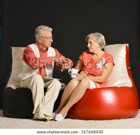 Happy senior couple sitting on armchairs