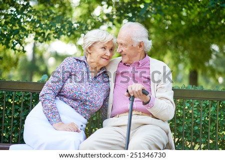 Happy senior couple sitting on bench in the park and talking