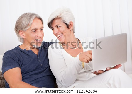 Happy senior couple sitting on sofa at home using laptop