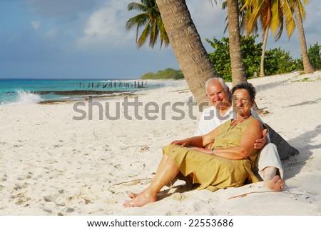 Happy senior couple sitting on the beach embracing each other, enjoying retirement on tropical destination: Maria la Gorda on caribbean island Cuba - stock photo
