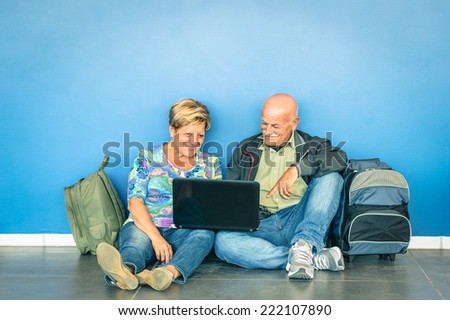 Happy senior couple sitting on the floor with laptop waiting for a flight at the airport - Concept of active elderly and interaction with new technologies - Travel lifestyle without age limitation - stock photo