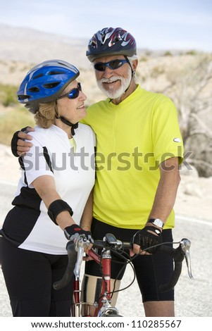 Happy senior couple standing by bicycle
