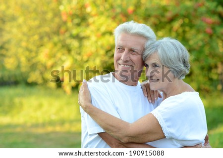 Happy senior couple standing in summer park