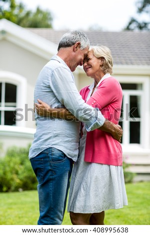 Happy senior couple standing with arms around outside house in yard - stock photo
