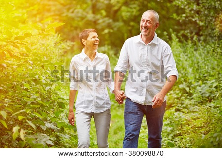 Happy senior couple taking a walk in summer in a forest - stock photo