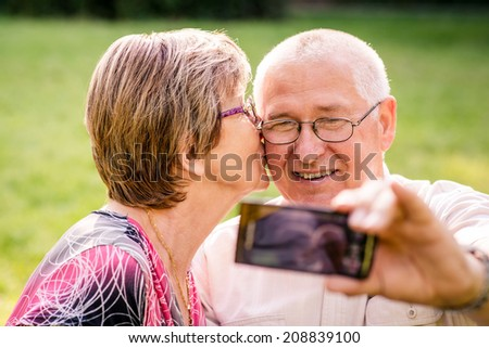 Happy senior couple taking picture of themselves by smartphone - woman is kissing man - stock photo