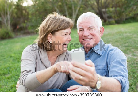 Happy senior couple taking selfies of eachother outside - stock photo