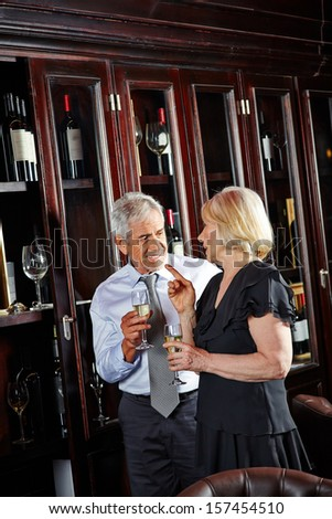 Happy senior couple together at a wine tasting event - stock photo