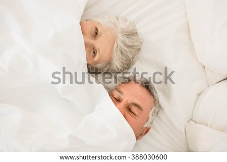 Happy senior couple under duvet in bed looking at the camera