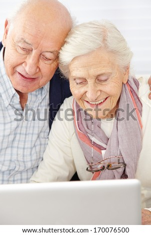 Happy senior couple using social media with laptop computer - stock photo