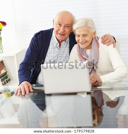 Happy senior couple using the internet together with a laptop computer