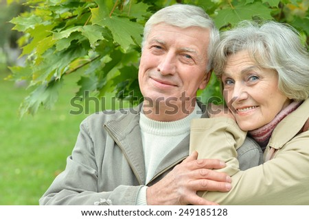 Happy senior couple walking in park - stock photo