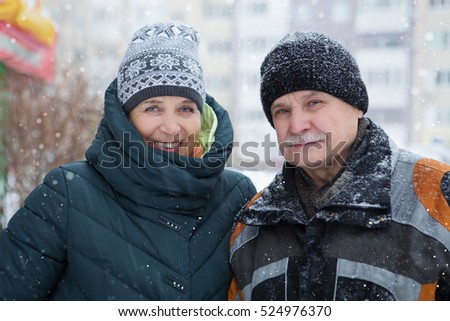 Happy senior couple walking in winter outdoors