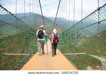 happy senior couple walking on the bridge in the nature park - stock photo