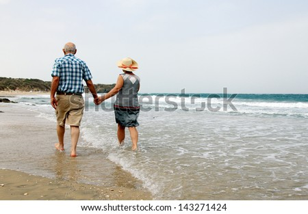 Happy senior couple walking together on a beach - stock photo