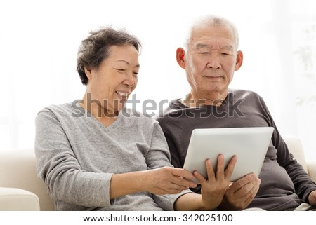 happy Senior Couple watching the tablet on sofa - stock photo