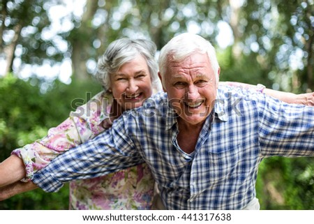 Happy senior couple with arms outstretched while standing in back yard - stock photo
