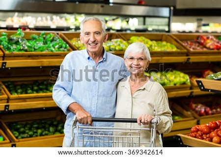 Happy senior couple with cart at the grocery shop - stock photo