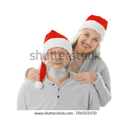 Happy senior couple with Christmas hats on white background