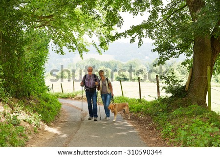 Happy senior couple with dog walking on hiking trail in summer - stock photo