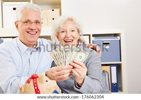 Happy senior couple with fan of dollar bills and a piggy bank - stock photo