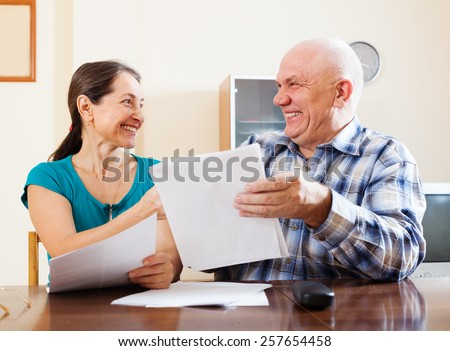 Happy senior couple with financial documents at home  - stock photo