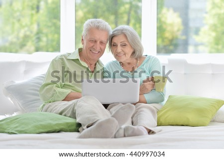 happy senior couple with laptop