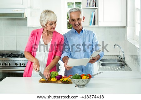 Happy senior couple with recipe book while preparing vegetables in kitchen - stock photo