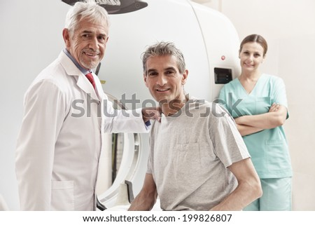 Happy senior doctor with his male patient at CT scanner machine. Female assistant on background.