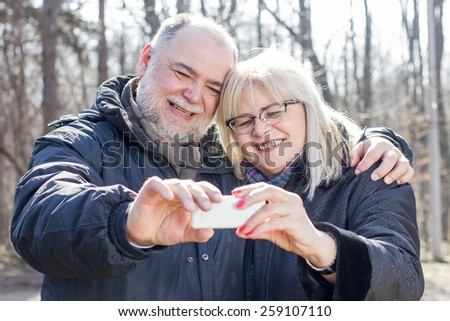 Happy Senior Elderly Couple taking Selfie with phone outdoor.Old people portrait in the park. - stock photo