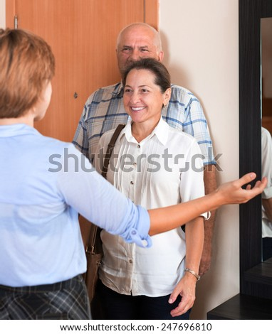 Happy senior family couple visiting adult daughter - stock photo