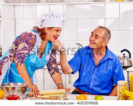 Happy senior family knead dough at kitchen. Many years together. - stock photo