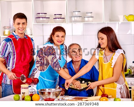Happy senior family with adult children cooking at kitchen. Two generations. - stock photo
