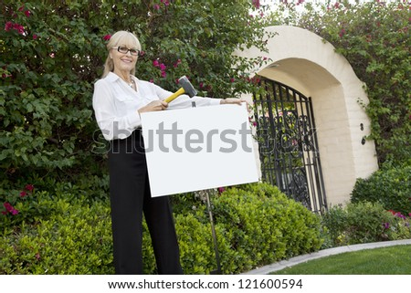 Happy senior female agent hammering sign board in lawn - stock photo